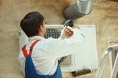 Hvac Technician Working On A Capacitor Part For Condensing Unit. Male Worker Or Repairman In Uniform poster