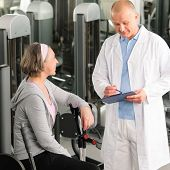 Physical therapist male assist active senior woman exercise at gym