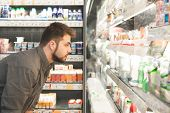 Man With A Beard Looks At Bottles Of Milk Products In A Supermarket. Adult Man Chooses Milk On The G poster