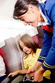 image of seatbelt  - Flight attendant helping a kid to fasten his seatbelt - JPG