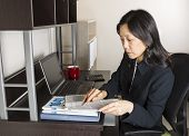 picture of cpa  - Professional Mature Asian woman doing income taxes with tax form booklet calculator coffee cup and computer on desk - JPG