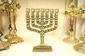 stock photo of tora  - Golden menorah and other religious symbols on display  - JPG