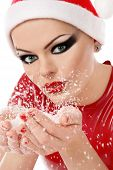 stock photo of latex woman  - Girl with heavy makeup in Santa hat and latex dress holding snowflakes in cupped hands - JPG