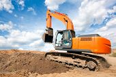 stock photo of construction machine  - Excavator machine moves with raised bucket on construction site during earth moving works - JPG
