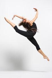 stock photo of ballet dancer  - young female dancer is jumping in black leotard - JPG