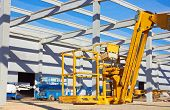 picture of arborist  - Hydraulic mobile construction platform elevated towards a blue sky - JPG