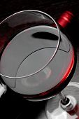image of low-necked  - top of view of red wine glass near bottle on black wood table  - JPG