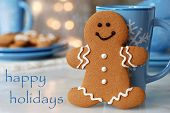 Holiday greeting card with smiling gingerbread man standing next to snowflake mug.  Plate of additio