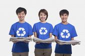 stock photo of medium-  length hair  - Three young people carrying newspapers - JPG