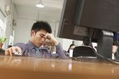 pic of late 20s  - exhausted businessman sitting in front of computer - JPG