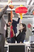 Coworkers hanging decorations in office for Chinese new year