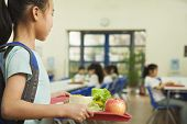 stock photo of first class  - School girl holding food tray in school cafeteria - JPG
