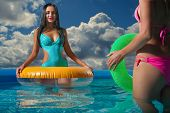 Two attractive slim and tanned young ladies with inflatable rings in swimming pool on vacation or ho