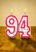 Burning birthday candles number 94 on a wooden background