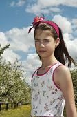 picture of sulky  - Girl in the sour cherry orchard with flowering trees around her looking sulky - JPG