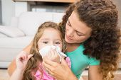pic of hay fever  - Mother helping her daughter blow her nose at home in living room - JPG