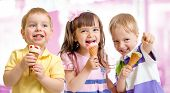 foto of threesome  - happy children or kids group with ice cream - JPG
