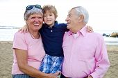 Happy Cute Kid Hugging Grandparents In Vacation