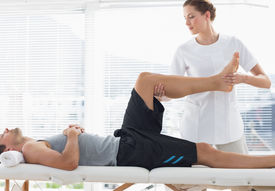 stock photo of physiotherapist  - Physiotherapist massaging leg of young man at spa - JPG