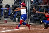 image of fastpitch  - young lady fastpitch softball player reaches with glove to catch the ball but the batter makes contact and hits the ball. 