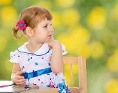 stock photo of montessori school  - Charming little girl reading a book while sitting at a table in the Montessori classroom - JPG