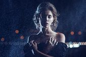 stock photo of night gown  - Beautiful woman in black dress posing on a city lights background - JPG