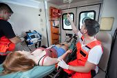 stock photo of paramedic  - Injured woman and paramedics in ambulance horizontal - JPG