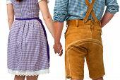 stock photo of lederhosen  - bavarian couple wearing traditional dress holding hands - JPG