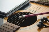 stock photo of guitar  - Notebook and pencil on guitar Writing music - JPG