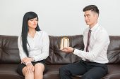 image of office romance  - Side view of Business couple in formal clothing sitting on sofa in office - JPG
