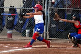 stock photo of fastpitch  - young lady fastpitch softball player reaches with glove to catch the ball but the batter makes contact and hits the ball.  ** note: slight graininess, best at smaller sizes - JPG