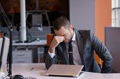 picture of frustrated  - frustrated young business man working on laptop computer at office - JPG