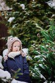 foto of snowy owl  - vertical portrait of adorable happy child girl in owl knitted hat on the walk in winter snowy garden - JPG