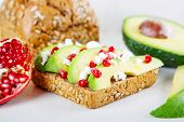 stock photo of sunflower-seeds  - Avocado with Feta pomegranate and olive oil on sunflower seeds bread sandwich - JPG