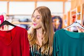 stock photo of boutique  - Woman choosing clothes on clothes rail in boutique or fashion store - JPG