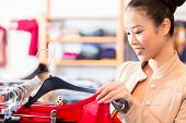 picture of boutique  - Woman choosing clothes on clothes rail in boutique or fashion store - JPG