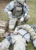 picture of army  - United States Army ranger treating the wounds of his injured fellow in arms - JPG