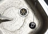 foto of sink  - Water flows from a tap in a stainless steel sink - JPG