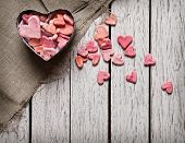 foto of heart  - Open heart shaped gift box with heap of small hearts inside and outside on white wooden background - JPG