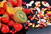 stock photo of pesticide  - Berries fruits vitamins and nutritional supplements on a black background - JPG
