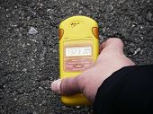stock photo of exclusive  - Checking radiation level with a personal dosimeter - JPG