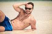 image of elbows  - Smiling young man lying on the beach while fixing his hair - JPG