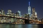 stock photo of freedom tower  - The New York City skyline at night w Brooklyn Bridge and Freedom tower - JPG