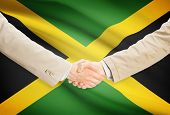 stock photo of jamaican flag  - Businessmen shaking hands with flag on background  - JPG