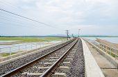 image of dam  - Railroad tracks into the reservoir Pa Sak Jolasid Dam Lopburi Thailand - JPG