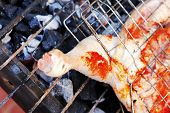 picture of charcoal  - grilling spiced chicken in grid on charcoal bbq with tomatoes and vegetables - JPG