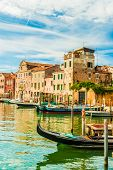 pic of gondola  - Beautiful colorful image of a canal in Venice with moorings and a gondola in the forefront and old houses under blue cloudy sky in the background - JPG