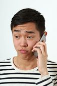 stock photo of disappointed  - Disappointed young Asian man using a smartphone - JPG