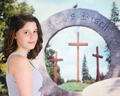 picture of he is risen  - A beautiful teen girl looking back at the viewer as she stands near an outdoor Christian Easter display  - JPG