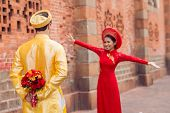 foto of fiance  - Rear view of man in traditional Vietnamese costume with bouquet of flowers for his fiance behind back - JPG